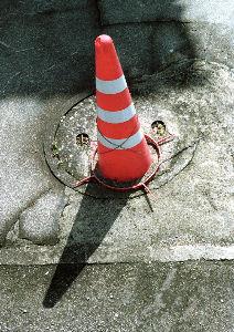 路上観察学 駐車場入り口に置かれたとんがり帽子のコーン。 長年の風雨と紫外線により四角い台座部分が破損して 照準