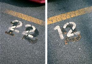 路上観察学 おそらく駐車場の拡張に伴い、古い番号を黒で塗りつぶして上書きしてある。 古い文字は区画線と同じ黄色で